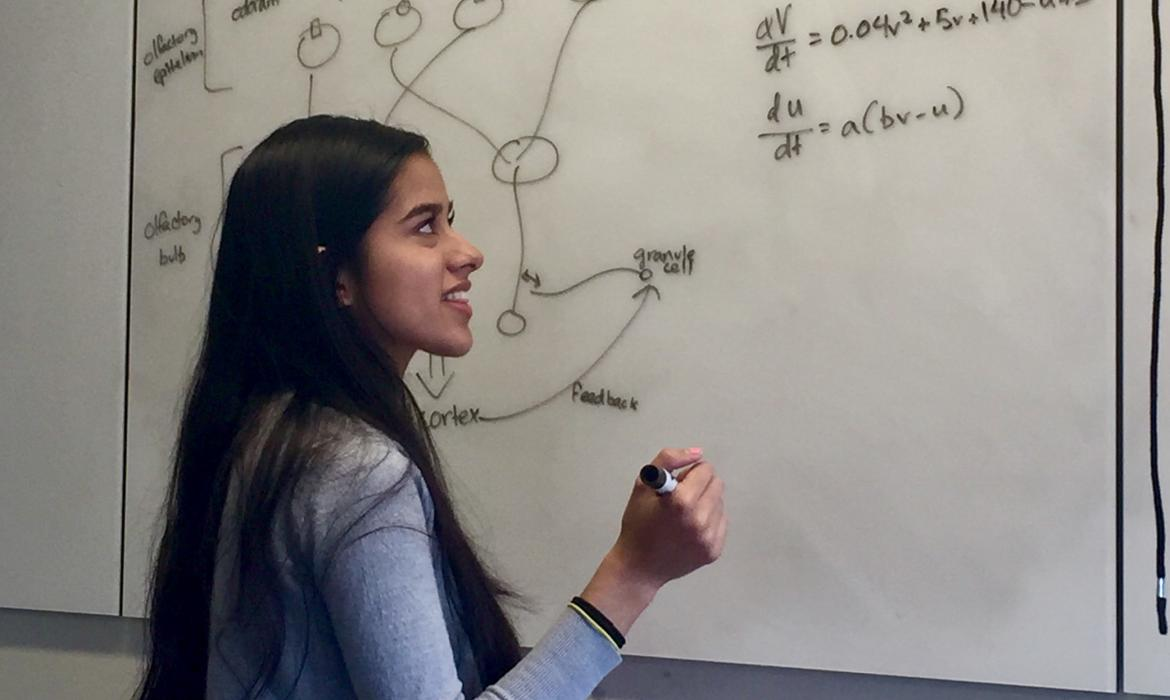 Sneha in front of whiteboard