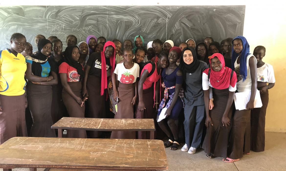 Fatima is posing with a group of students in a classroom.