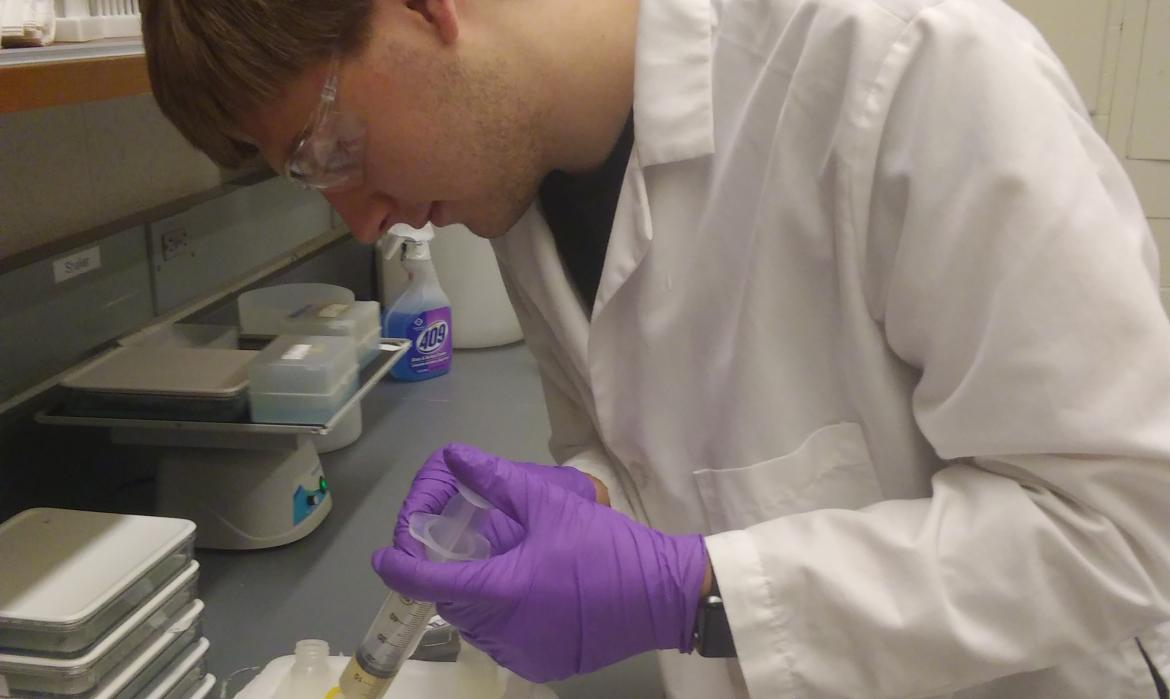 Samuel Botterbusch in the lab  using a pipette