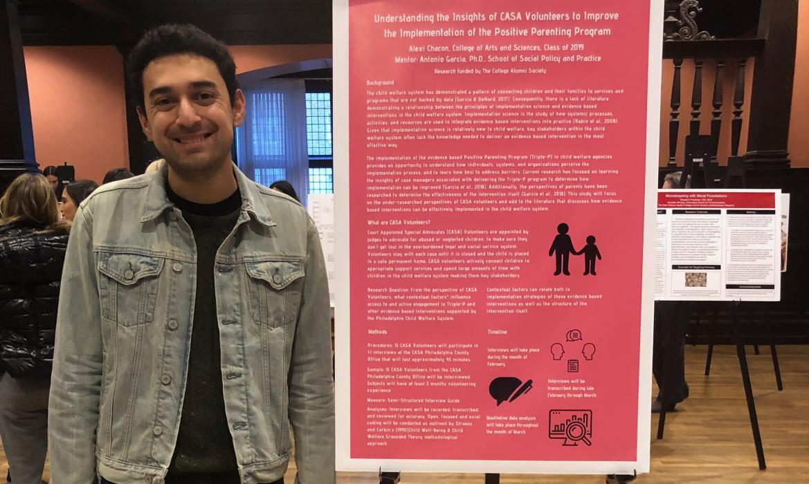 Alexi posing in front of his poster.