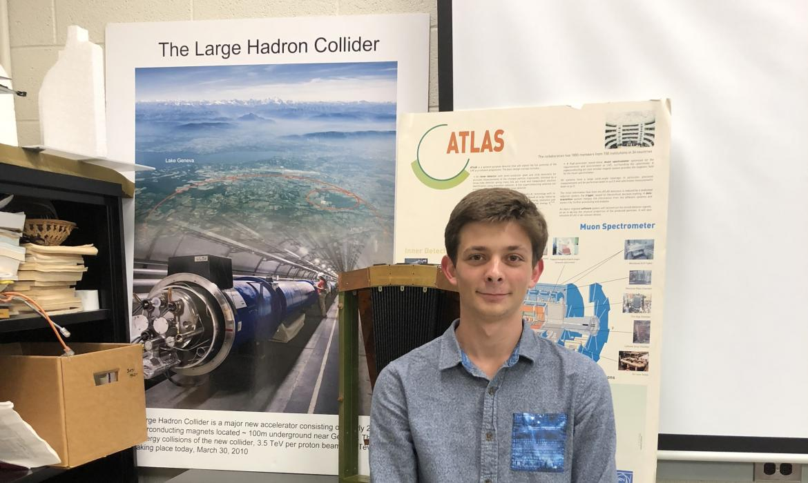 Sam in front of poster of LHC