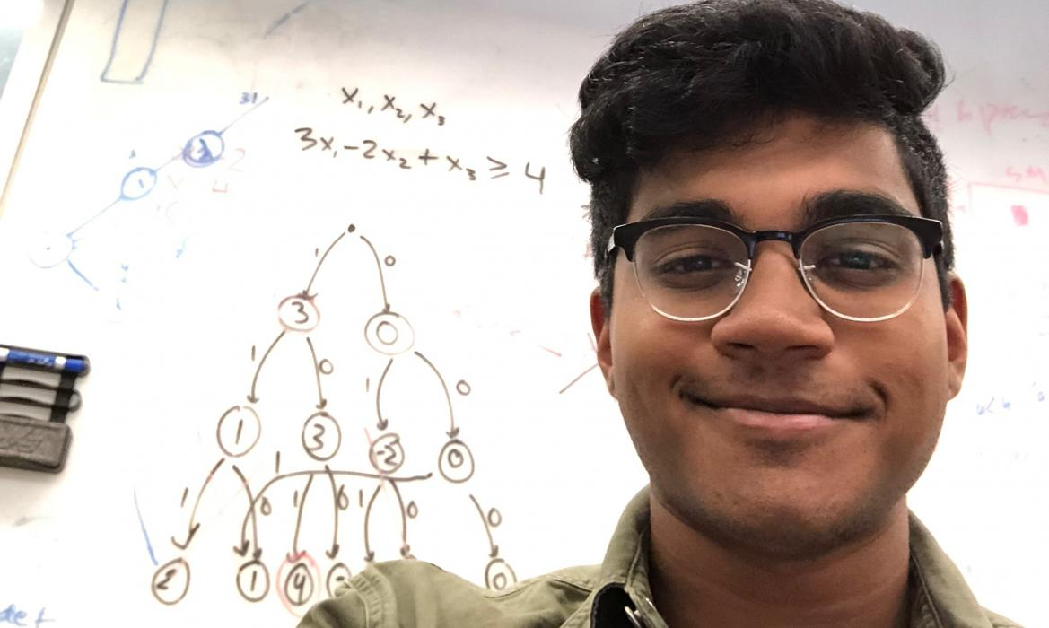 Arun in front of representation of neural network
