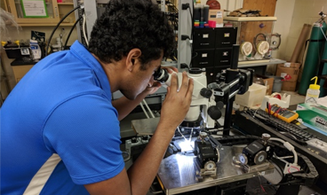 Adithya looking into a microscope.