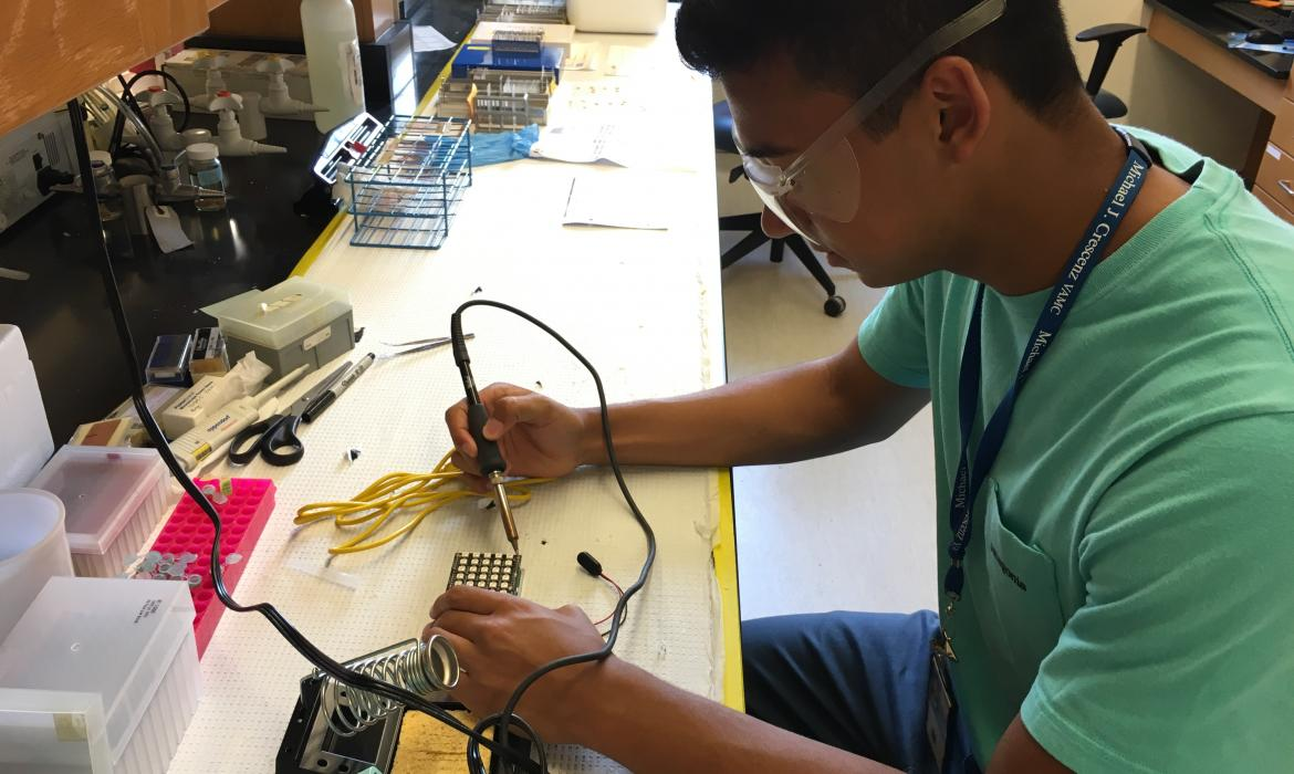 Vishal working on a soldering bench