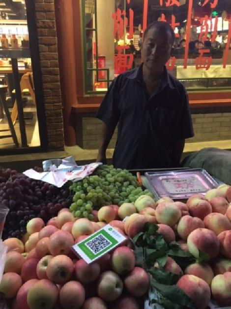 The laminated card on the fruit stand is scanned by one's cell phone to pay.  Nearly all transactions, including taxis and large department stores, are made using this system.  Cash is now rarely seen.